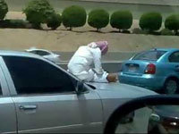 Saudi Man Texting on Hood of Moving Car